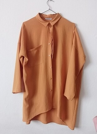 Koyu sarı tunik şeklinde bir gömlek, salaş, dökümlü kumaş